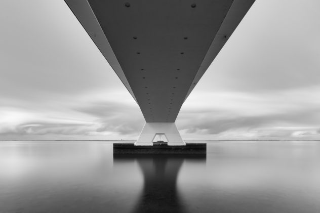 A Dutch coastal landscape in B&W, showing the underside of the Zeelandbrug (Zeeland Bridge) in The Netherlands against a cloudy sky in the back. Under the Bridge - Copyright 2020 Johan Peijnenburg - NiO Photography