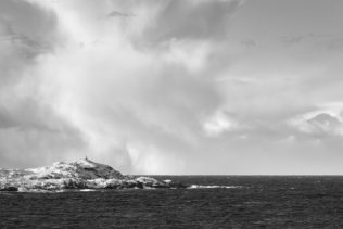 The coast of Lofoten in black & white, featuring a small lighthouse on an island with snow and dramatic storm clouds in the back. Incoming - Copyright 2020 Johan Peijnenburg - NiO Photography