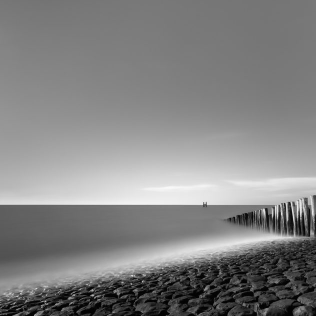 The Dutch coast in Westkapelle, Zeeland, with rocks in the foreground and a breakwater leading the eye to a pole in the North Sea. Captured in black & white. At the Sea - Copyright 2020 Johan Peijnenburg - NiO Photography