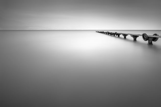 A lake landscape in  B&W, featuring an old abandoned pier in a lake on a mystical  foggy day (Lac de Neuchâtel in Switzerland). Abandoned - Copyright Johan Peijnenburg - NiO Photography