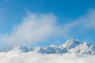 A winter mountain landscape, featuring the jagged peaks of the mountains of the Mont Blanc massif above a bank of clouds. Grand - Copyright Johan Peijnenburg - NiO Photography