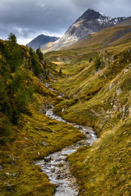 An autumnal landscape, featuring brewing dark clouds above a meadow with a meandering mountain river in the Alps of Graubünden in Switzerland. Up the Stream - Copyright Johan Peijnenburg - NiO Photography