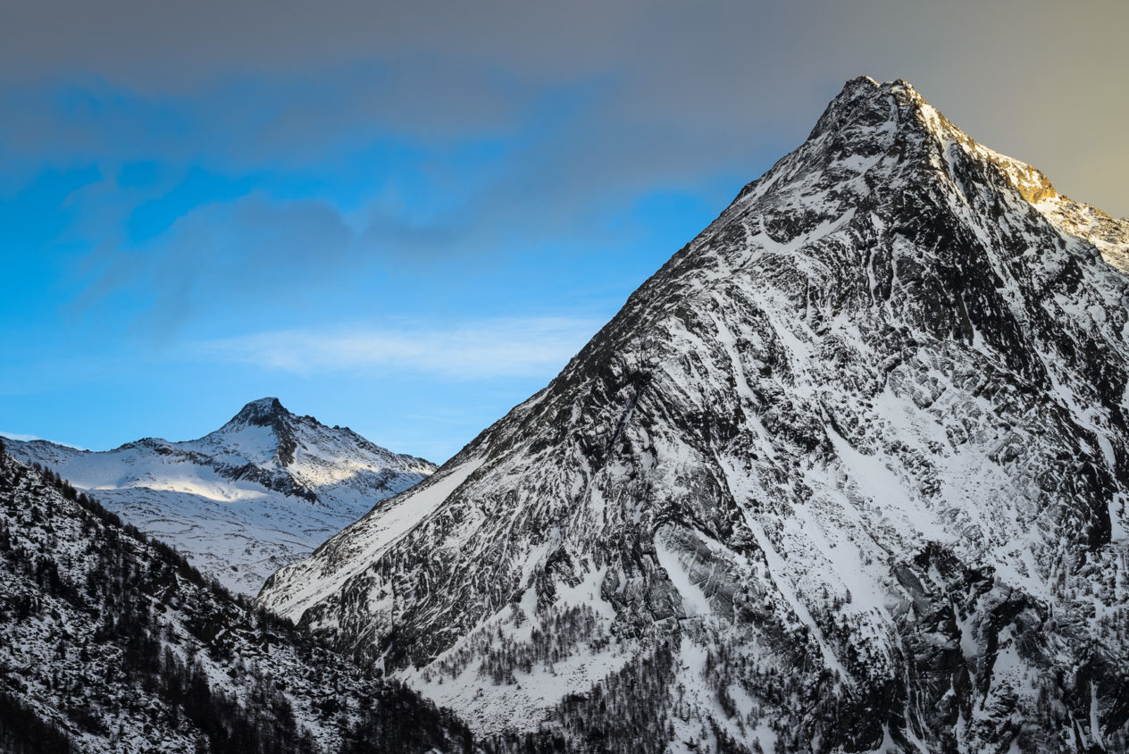 An Alpine winter mountain landscape in colour, featuring two Swiss Alps at sunset with patches of mountain light warming the landscape sideways. Both mountains are located near Saas Fee in Switzerland. Patches of Mountain Light - Copyright Johan Peijnenburg - NiO Photography