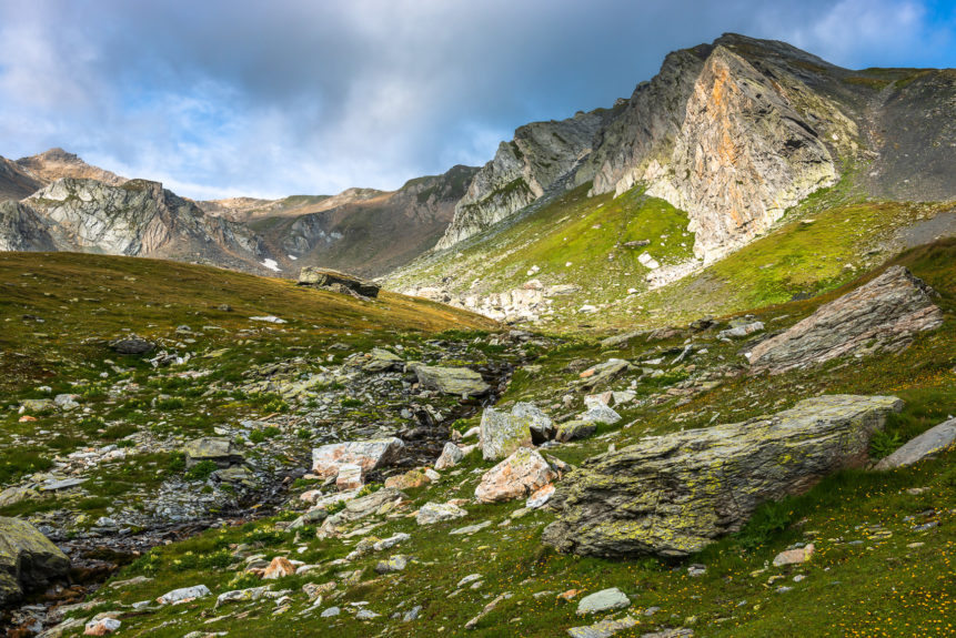 A rocky alpine meadow and the mountains of the Italian Alps (Pointe de Drône) catching first morning light just after sunrise. Early Ascent - Copyright Johan Peijnenburg - NiO Photography