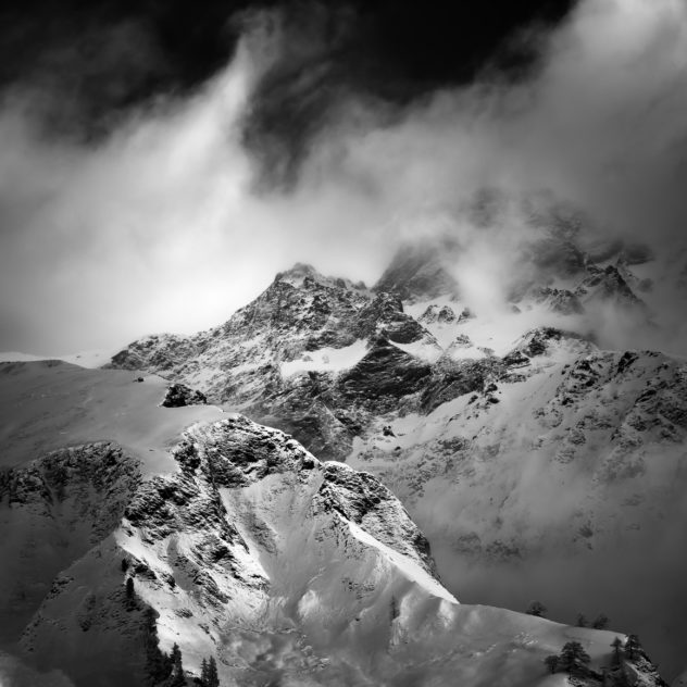 A Swiss mountain landscape in B&W, featuring La Tsavre mountain in winter, surrounded by clouds and fog, near La Fouly in Switzerland. Mystic Mountain - Copyright Johan Peijnenburg - NiO Photography