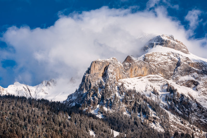 A winter mountain landscape near Gsteig in the Swiss Alps, with snow and clearing fog above an alpine forest and the Spitzhorn. Unveiled - Copyright Johan Peijnenburg - NiO Photography