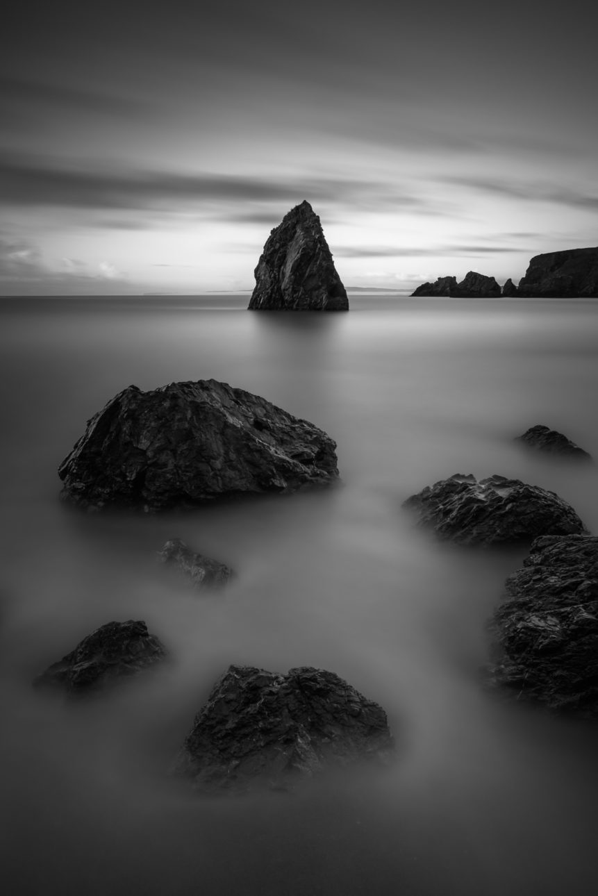 An Irish coastal landscape in B&W, featuring the rocks and sea stacks of Ballydowane Cove at the Celtic Sea in County Waterford, Ireland. The Cove - Copyright Johan Peijnenburg - NiO Photography