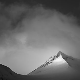 An intimate mountain landscape in black & white, featuring the snowy peak of Bellavista mountain kissed by soft morning light near Pontresina in the Swiss region of Engadin. Kiss of Light - Copyright Johan Peijnenburg - NiO Photography