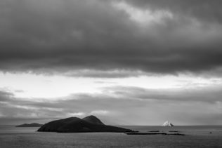 A coastal landscape in B&W with first morning light warming Tearaght Island during a moody sunrise at the Blasket Islands near the Dingle Peninsula in Ireland. Awakening - Copyright Johan Peijnenburg - NiO Photography