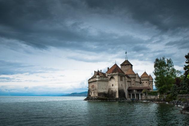 A lake landscape, featuring dark clouds above Château de Chillon and Lac Léman (Lake Geneva) near Montreux. Château de Chillon - Copyright Johan Peijnenburg - NiO Photography