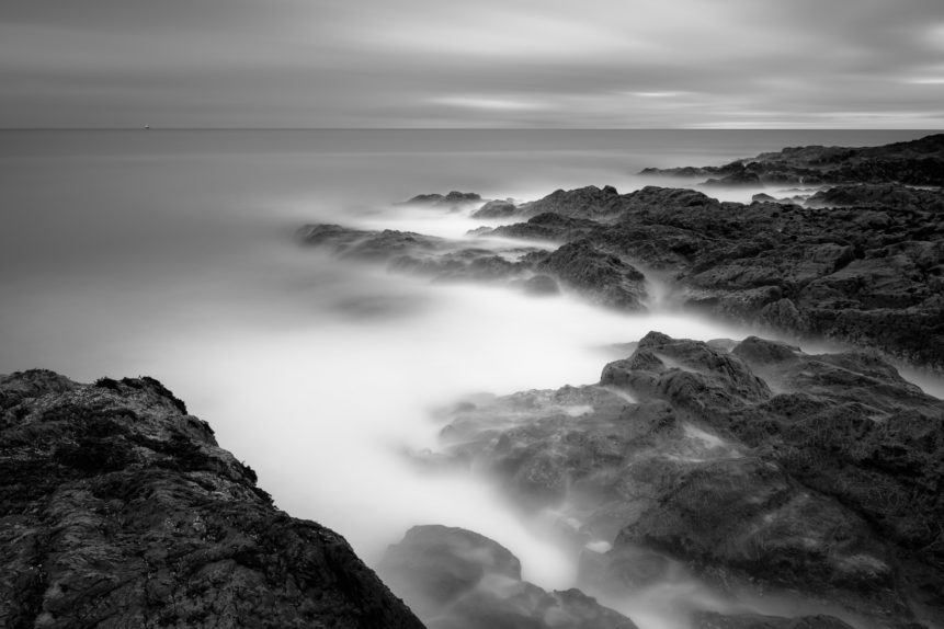 The Irish Sea coast in B&W, with a passing freight ship and the rugged shores near Greystones Beach in Wicklow, Ireland. An Irish Point of View - Copyright Johan Peijnenburg - NiO Photography