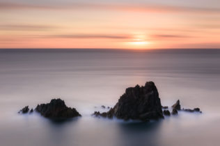 Cliffs and a colourful sunset at the Irish coast of the North Atlantic Ocean near Slea Head in Dingle, County Kerry, Ireland. Staring at the Sun - Copyright Johan Peijnenburg - NiO Photography