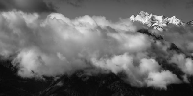 A black and white landscape showing the Swiss mountain peaks Dom, Nadelhorn and Täschhorn, lit by early morning light above a layer of clouds and fog. High above the Clouds - Copyright Johan Peijnenburg - NiO Photography