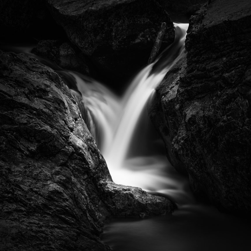 A silky smooth waterfall in a dark cave, with water from a mountain creek dancing around the granite rocks, in black & white. Dancing in the Dark - Copyright Johan Peijnenburg - NiO Photography