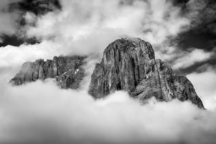 A mountain landscape in B&W, featuring Sassolungo (Langkofel) in the Dolomites of South Tyrol in Italy enclosed by clouds and fog. Dramatic - Copyright Johan Peijnenburg - NiO Photography