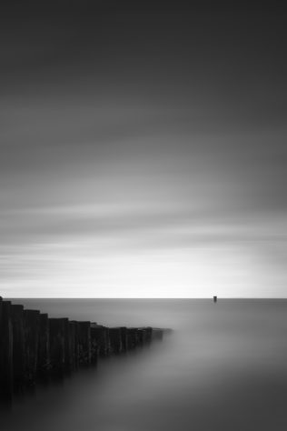 A minimalist Dutch coastal landscape in B&W, with a breakwater in The North Sea leading the eye to a pole and the moody sky at the horizon. Breaking Waves - Copyright Johan Peijnenburg - NiO Photography