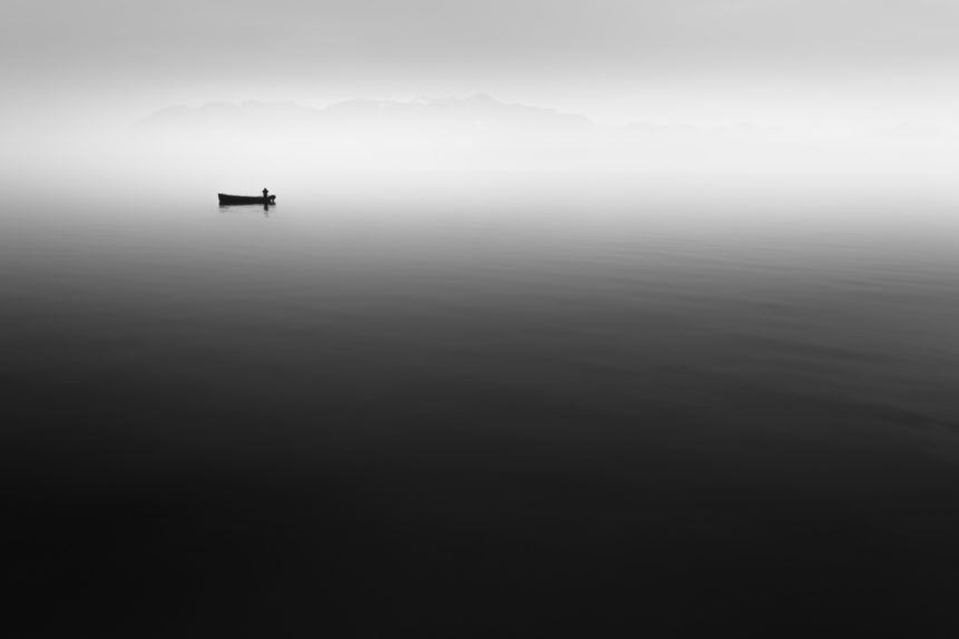 A fisherman at work on his boat on a misty Lac Léman (Lake Geneva) in Switzerland with the French Alps in the background. A Day at the Office - Copyright Johan Peijnenburg - NiO Photography