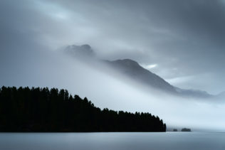 A lake landscape, showing Piz de la Margna with magical light and a fog phenomenon called the Maloja Snake at Lake Sils in Switzerland. Engulfed - Copyright Johan Peijnenburg - NiO Photography