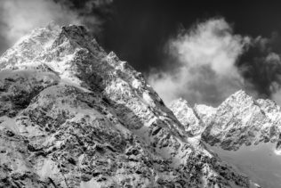 A Swiss mountain landscape in B&W, showing an alpine winter landscape with rising fog around the mountains of the Mont Blanc massif. Snowy Peaks - Copyright Johan Peijnenburg - NiO Photography