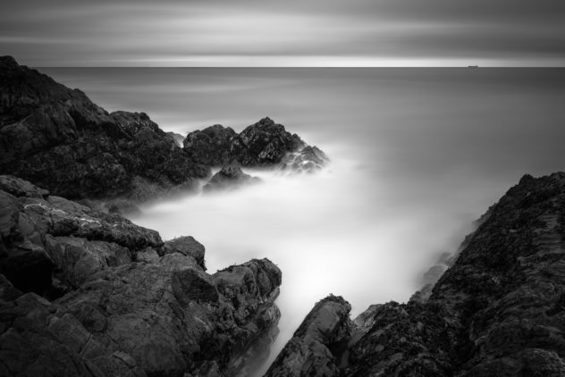 An Irish coastal landscape in black & white showing the rugged cliffs of Greystones Beach and a freight ship in the Irish Sea near Wicklow, Ireland. In the Distance - Copyright Johan Peijnenburg - NiO Photography