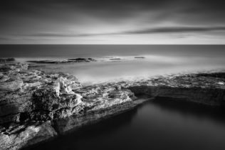 A black & white coastal landscape featuring the rock formations of the rugged Irish coast near Hook Head in County Wexford at sunset. Force of Nature - Copyright Johan Peijnenburg - NiO Photography