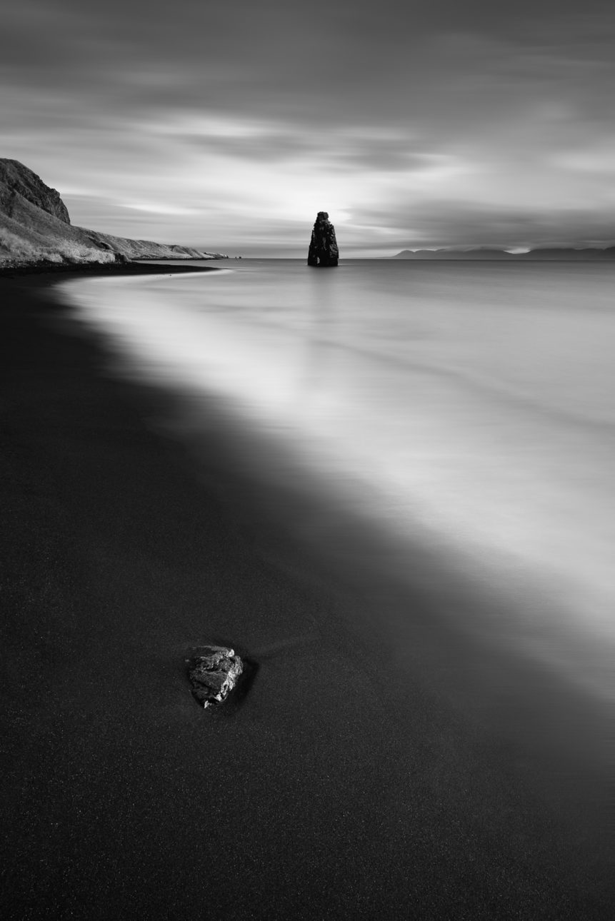 A black sand beach with a rock and Hvítserkur, a basalt sea stack at the eastern shore of the Vatnsnes peninsula in northwest Iceland, in a coastal landscape in B&W. The Troll - Copyright Johan Peijnenburg - NiO Photography