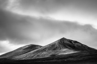 A minimalist Icelandic landscape in B&W, featuring the black sand and mountains of Landmannalaugar in the highlands of Iceland against a moody sky. Icelandic Curves - Copyright Johan Peijnenburg - NiO Photography