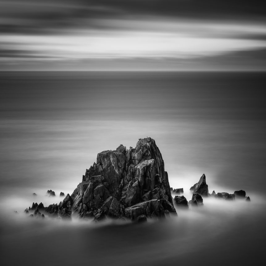 An Irish coastal landscape in B&W, featuring a seagull and rugged pointy cliffs in the North Atlantic Ocean near Slea Head on the Dingle peninsula in Kerry, Ireland. To the Point - Copyright Johan Peijnenburg - NiO Photography