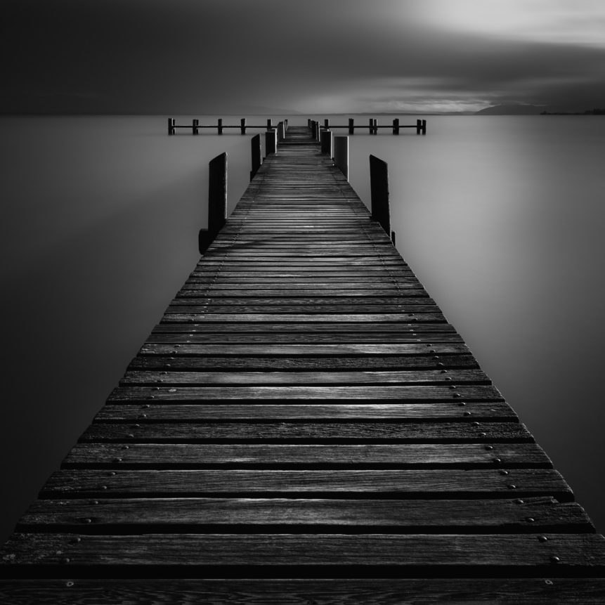 A wooden pier in Lac Léman (Lake Geneva) at Préverènges beach during sunset, in black & white. Shadows & Light - Copyright Johan Peijnenburg - NiO Photography