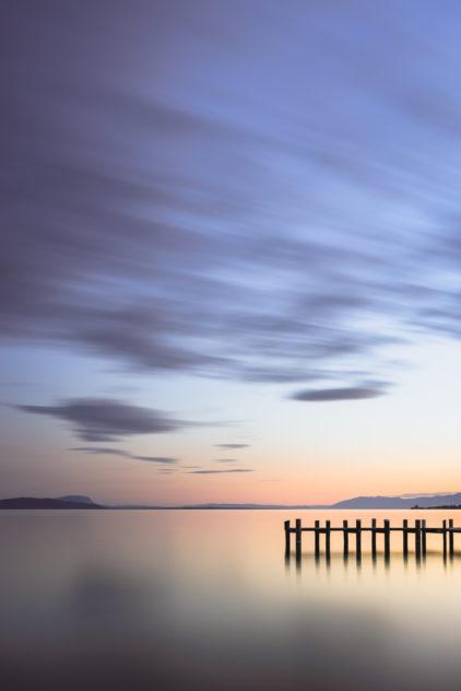 A lake landscape featuring a colourful sunset at Lac Léman (Lake Geneva), with a wooden pier, near Préverenges in Switzerland. Colourful tranquillity at Lac Léman - Copyright Johan Peijnenburg - NiO Photography