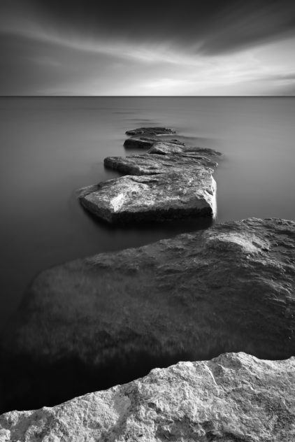 A lake landscape in B&W featuring a line of rocks acting as a breakwater in Lac Léman (Lake Geneva). Walk on Water - Copyright Johan Peijnenburg - NiO Photography
