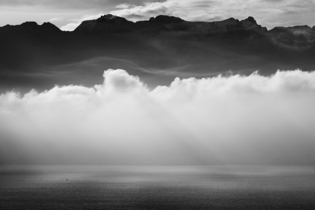 A lake landscape in black & white of Lac Léman and the Alps, with  a sailing boat and the lake lit by sunbeams passing through fog and clouds. Feeling Small - Copyright Johan Peijnenburg - NiO Photography