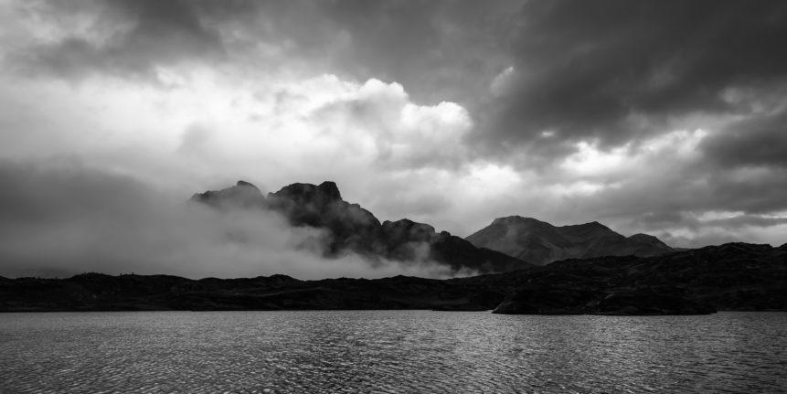 A moody mountain lake sunset at Laghetto Moesola, a small Swiss lake situated at the summit of the San Bernardino Pass. In the background the mountains Piz Uccello and Piz de la Lumbreida. Mountain Moods - Copyright Johan Peijnenburg - NiO Photography