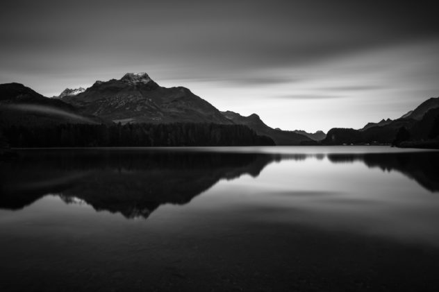 A lake landscape in B&W, featuring the Swiss Alps around Piz de la Margna mountain at sunrise with alpenglow on the peaks and the mountain range reflected in Lake Sils (Silsersee). First Light - Copyright Johan Peijnenburg - NiO Photography