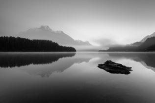 A sunrise with the reflections of mountains and a larch tree forest in Lake Sils (Silsersee, Lej da Segl), a mountain lake in the Alps. Enjoy the Silence - Copyright 2016 Johan Peijnenburg