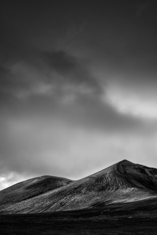 A fine art mountain landscape in B&W, featuring a foreboding sky above the eroded mountains of Landmannalaugar in the highlands of Iceland. Eroded - Copyright Johan Peijnenburg - NiO Photography