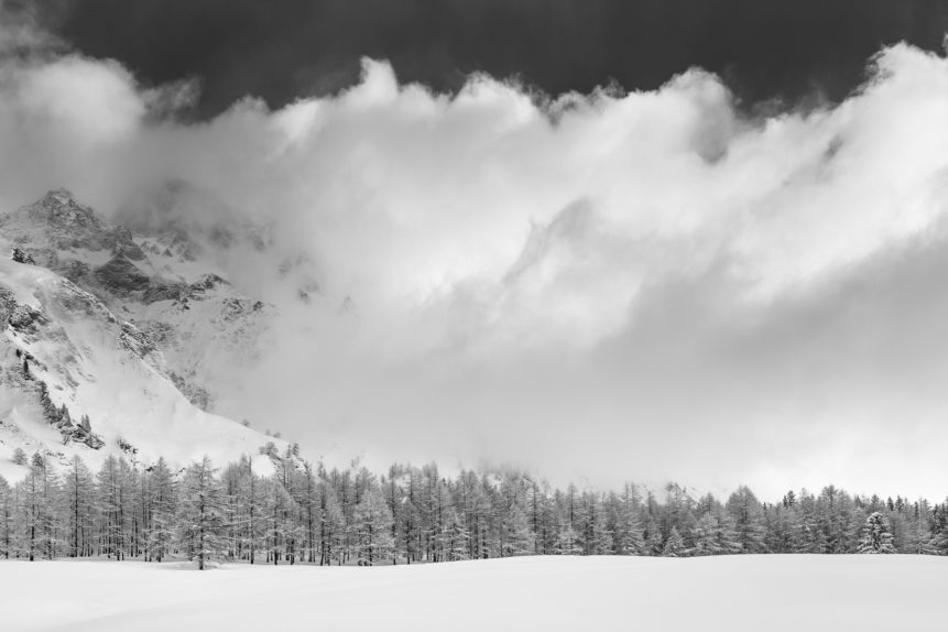 An alpine landscape in B&W, featuring a larch tree forest with snow, the Swiss mountain La Tsavre and a big cloud of rising fog, near La Fouly in the Swiss Alps. The Wall - Copyright Johan Peijnenburg - NiO Photography