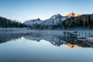 A Swiss mountain lake landscape, featuring a sunrise with alpenglow, a pier and mountain reflections at Lej da Staz (Stazersee) in St. Moritz. A Chilly Rise - Copyright Johan Peijnenburg - NiO Photography