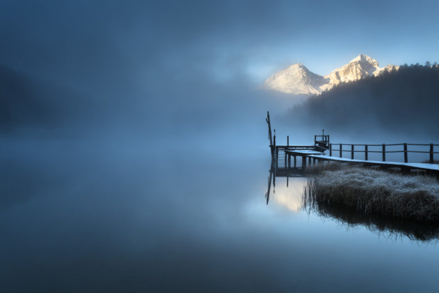 A lake landscape, featuring a misty sunrise at Lej da Staz (Stazersee) with fog, reflections of snow-covered mountains and a wooden pier. Lej da Staz is a small lake in the Swiss Alps near St. Moritz, Switzerland. Misty dawn - Copyright Johan Peijnenburg - NiO Photography
