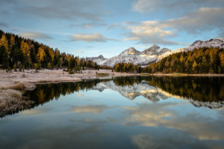 A lake landscape showing a tranquil and colourful sunrise at Lej da Staz (Stazersee) with trees in fall colours and snow on the Swiss Alps. Tranquil Sunrise - Copyright Johan Peijnenburg - NiO Photography