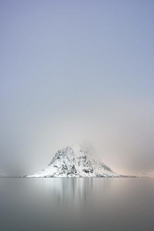 A Nordic coastal landscape, featuring Pantaliatinden mountain with snow and fog in the Kirkefjorden near Reine in Lofoten, Norway. Frozen Silence - Copyright Johan Peijnenburg - NiO Photography
