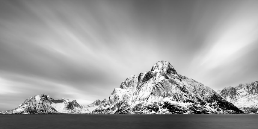A fine art mountain landscape in black & white, featuring the coastal mountains of Lofoten along the Kirkefjorden near Reine in Norway. Striking - Copyright Johan Peijnenburg - NiO Photography