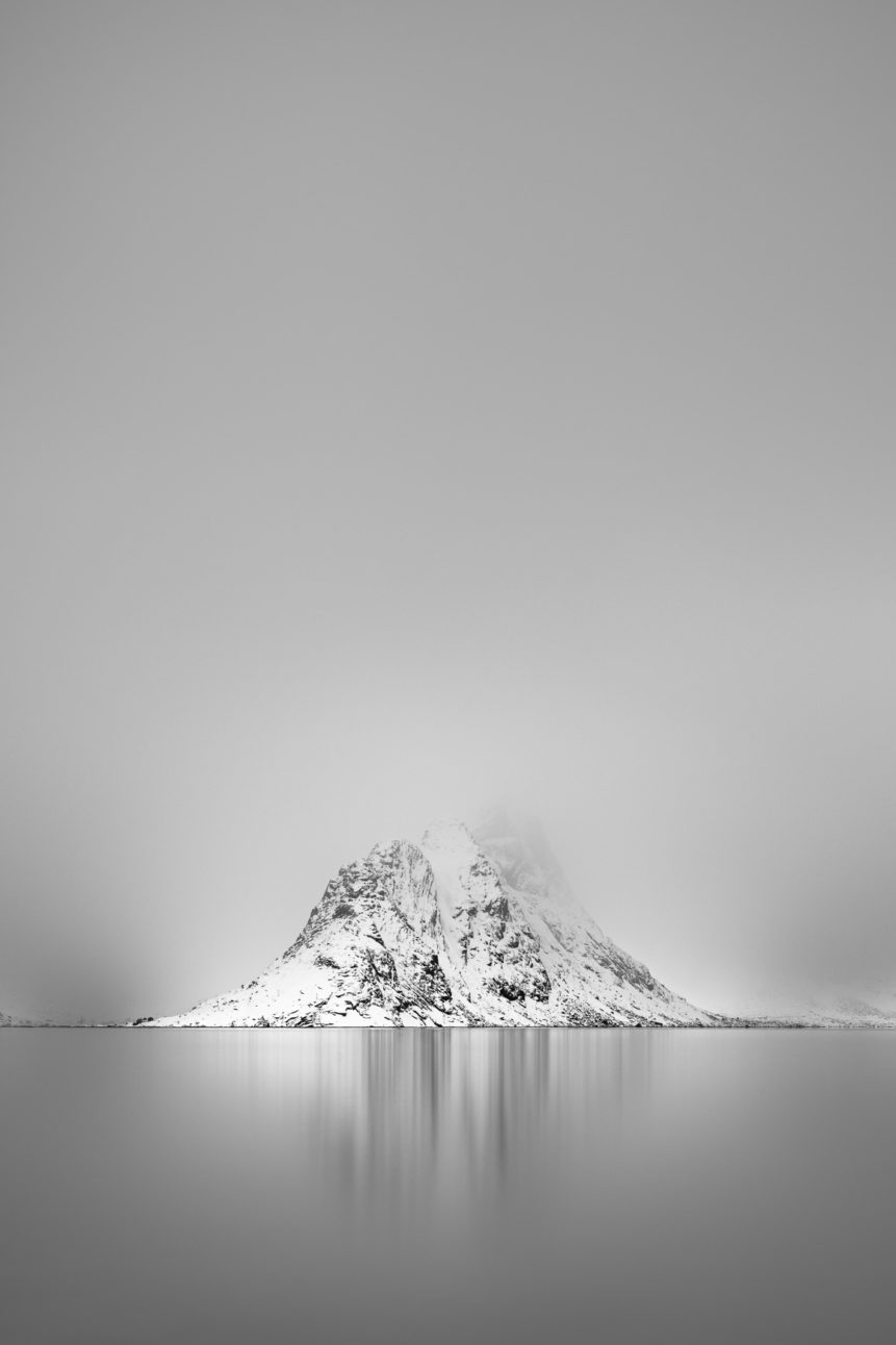 A Nordic coastal landscape in B&W,with last light warming Pantaliatinden mountain at the Kirkefjorden (Kjerkfjorden) in Lofoten, Norway. Reflections in Silver - Copyright Johan Peijnenburg - NiO Photography