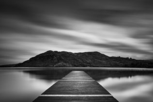 A fine art photograph in black & white, showing a lake landscape with hills and a wooden pier in Lough Caragh in Killarney National Park in Kerry, Ireland. The Landing - Copyright Johan Peijnenburg - NiO Photography