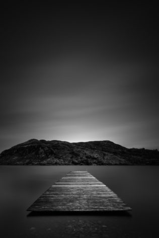 An Irish lake landscape in black & white, featuring a pier in Lough Caragh and the hills of Killarney National Park in County Kerry, Ireland. Afloat - Copyright Johan Peijnenburg - NiO Photography