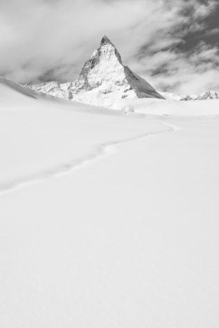 The Matterhorn (Cervino) in winter with a snow trail leading the eye towards the Matterhorn, in black & white. Standing Out - Copyright Johan Peijnenburg - NiO Photography