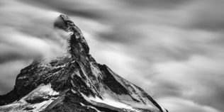 A mountain landscape in black & white, featuring the east and north faces of the iconic Matterhorn (Cervino) with snow, fog and clouds. Iconic - Copyright Johan Peijnenburg - NiO Photography