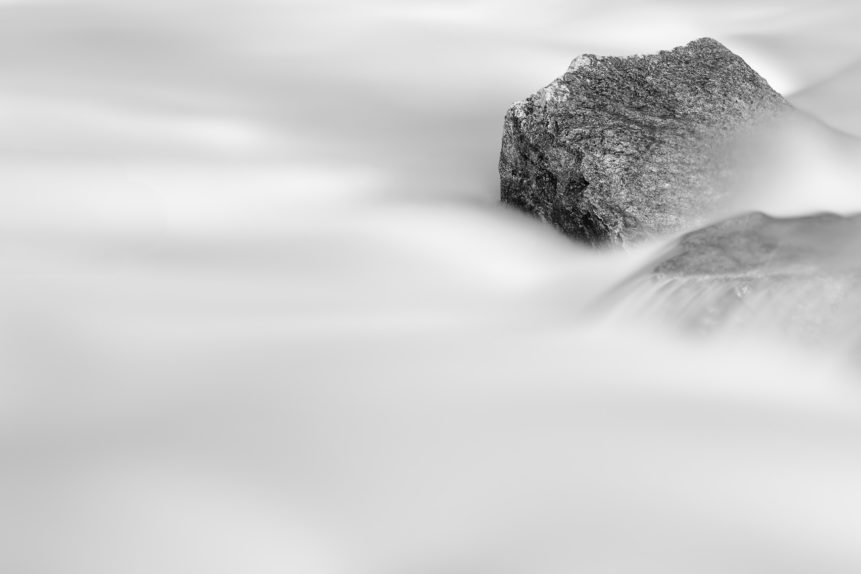 Granite rocks surrounded by the milky water of a glacial mountain river rapid, in a minimalist black and white fine art photograph. Smooth as Silk - Copyright Johan Peijnenburg - NiO Photography