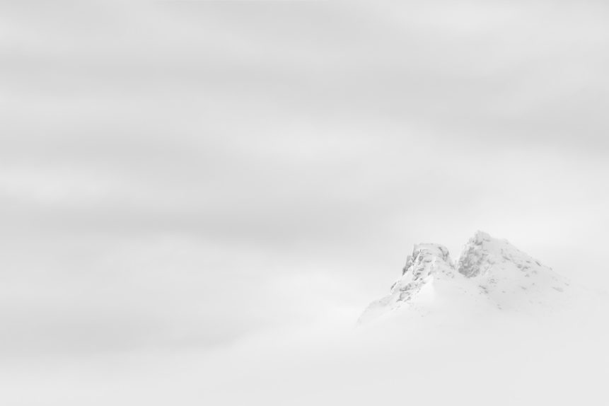 A fine art photograph in black & white, showing a misty mountain landscape with two snow-covered peaks surrounded by thick fog and clouds in Lofoten, Norway. A Glimpse - Copyright Johan Peijnenburg - NiO Photography