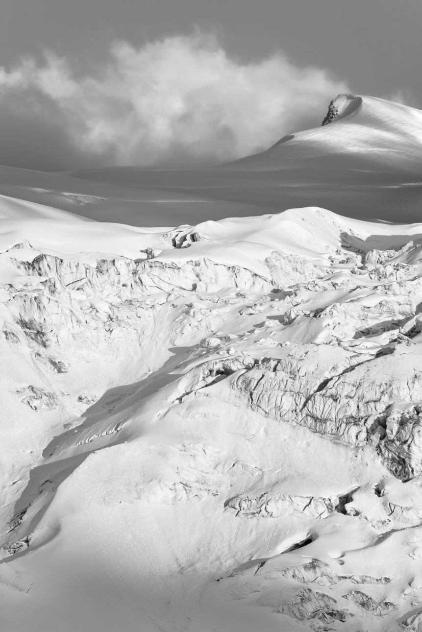 A mountain landscape in B&W, featuring the Moiry glacier with soft sunset light on the glacial snow and ice as well as Les Bouquetins mountain. Wall of Snow - Copyright Johan Peijnenburg - NiO Photography